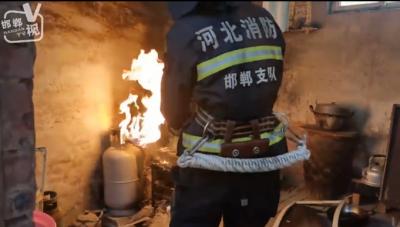 """邯郸V视 邯郸:村民家中煤气罐起火 消防员徒手拎""""火雷"""""""